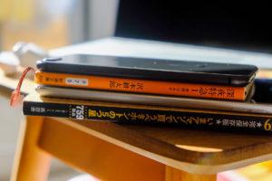 初代iPad miniと本の厚さを比べているの画像